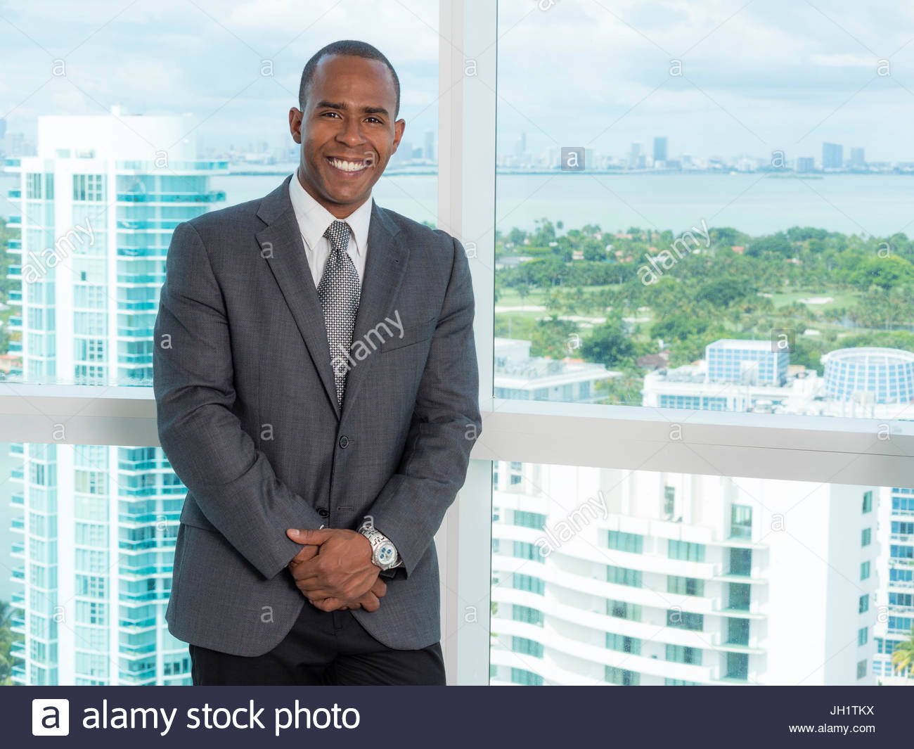 African descent businessman man standing in office building. More buildings can be seen in background - Stock Image