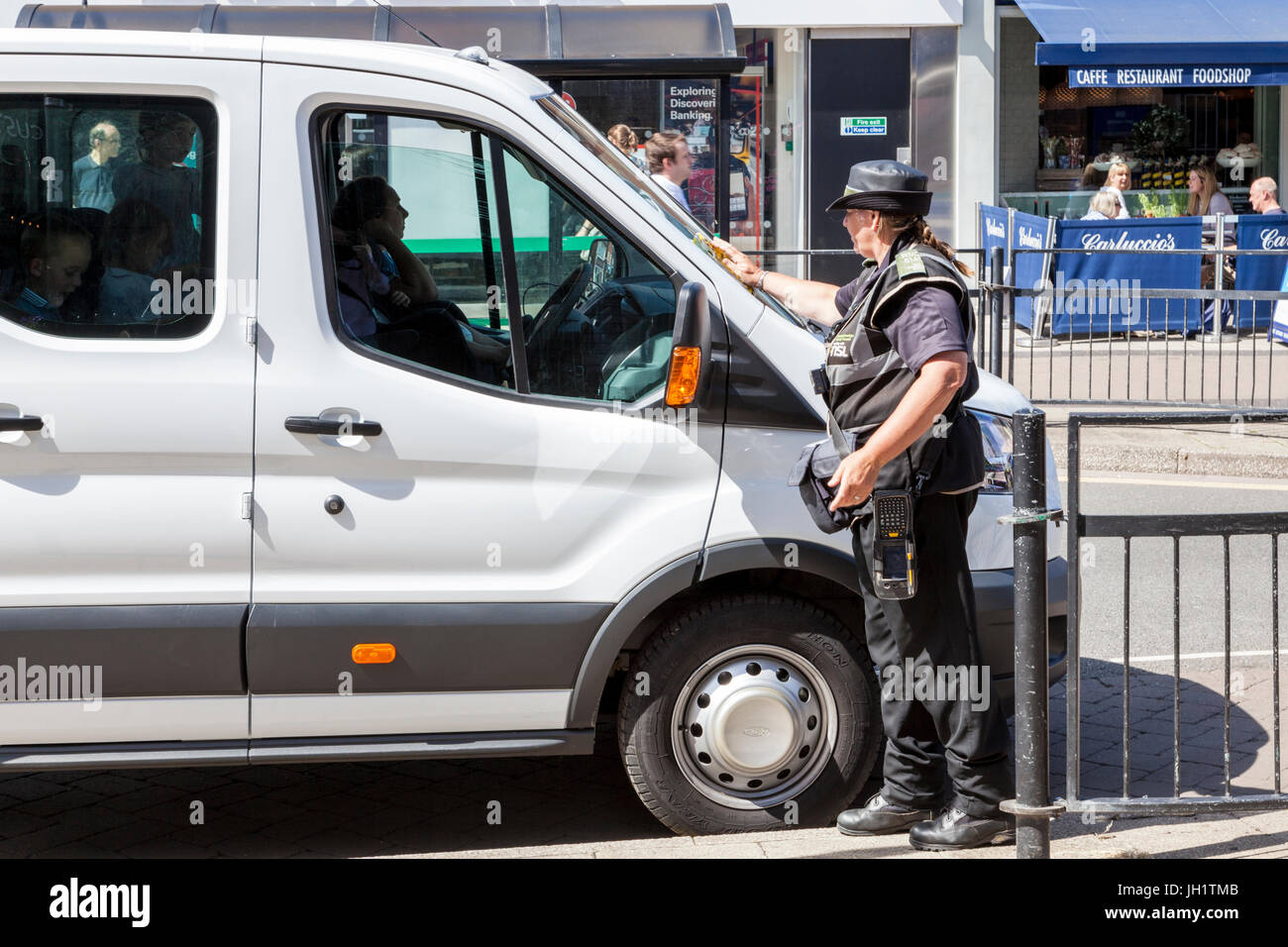Traffic warden issuing a parking ticket and attaching to a vehicle for illegal parking, West Bridgford, Nottinghamshire, - Stock Image