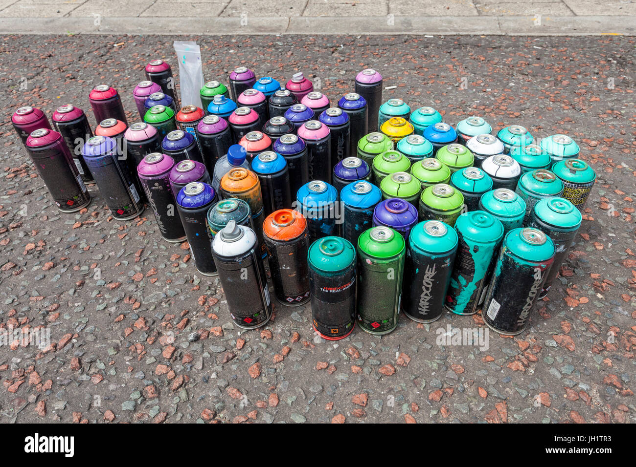 Used Hardcore aerosol spray paint cans - Stock Image