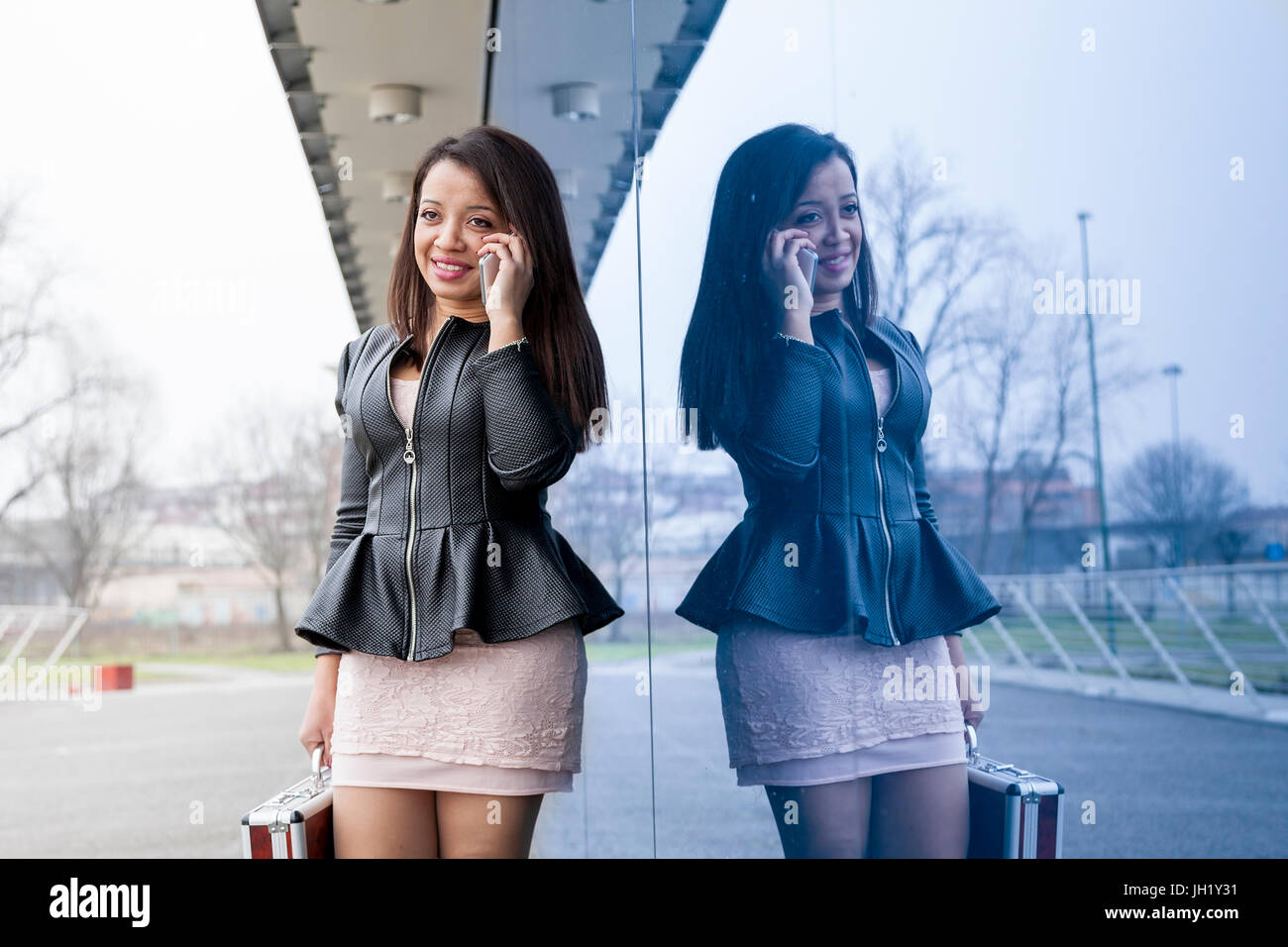 business woman talking on mobile smart phone outside - Stock Image