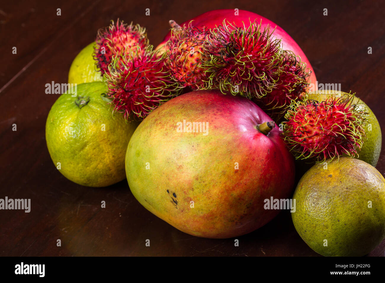 tropical fruit on a kitchen table including mangoes, juicing oranges and colorful rambutan - Stock Image