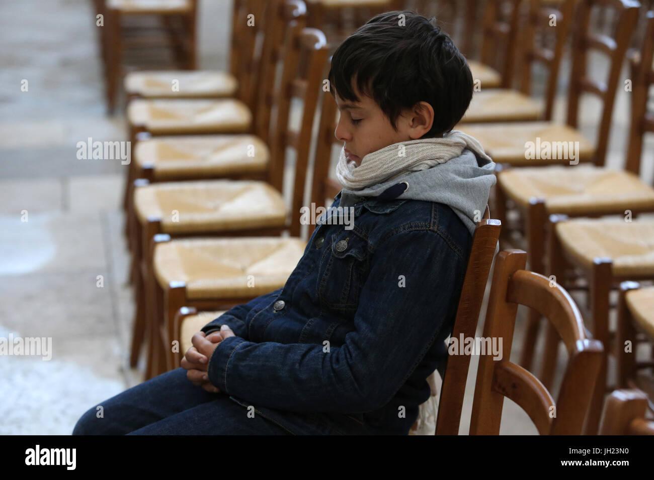 11-year-old boy in church. France. Stock Photo