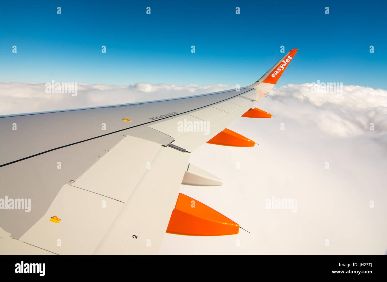 Orange and white wing on an Easyjet Airbus rising above white fluffy clouds. - Stock Image