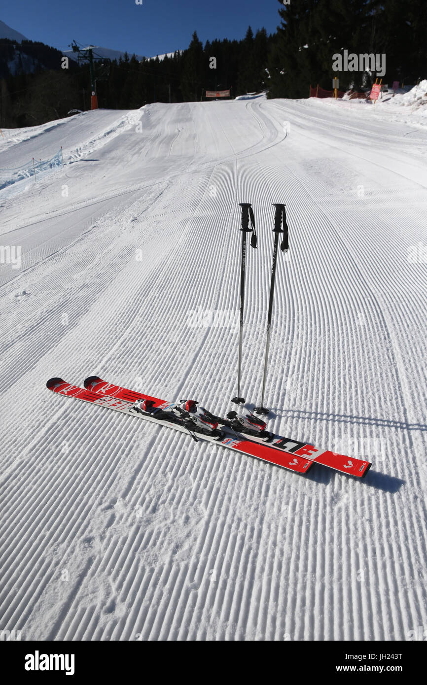 French Alps.  Skis and poles stuck in the snow. Groomed Ski Piste. France. - Stock Image