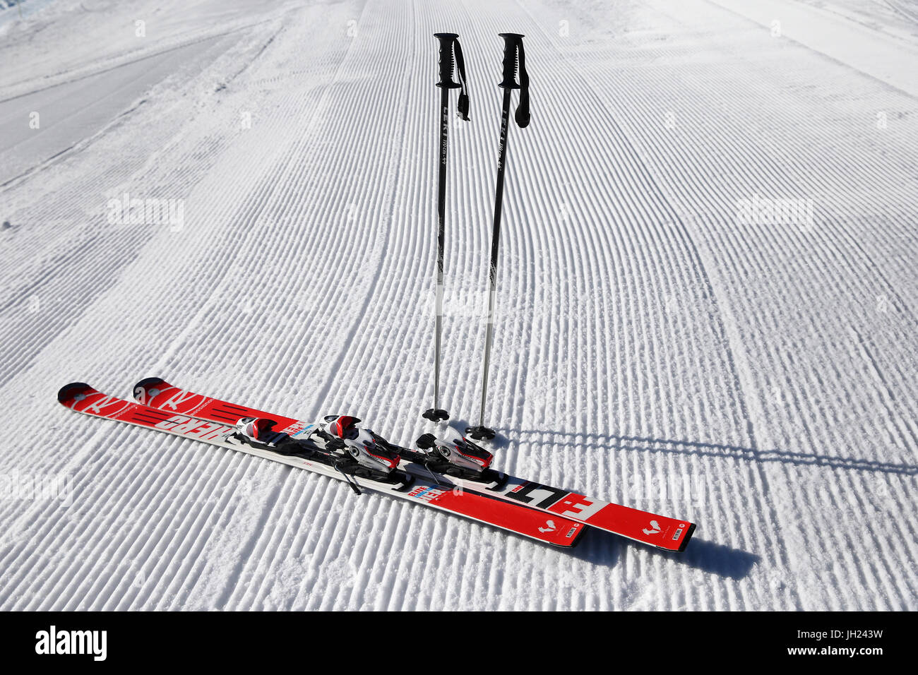 French Alps.  Skis and poles stuck in the snow. Groomed Ski Piste France. - Stock Image