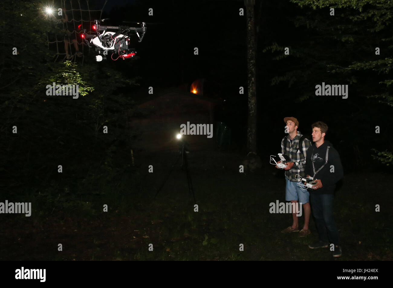 Pilots operating a drone with a camera at night. France. - Stock Image