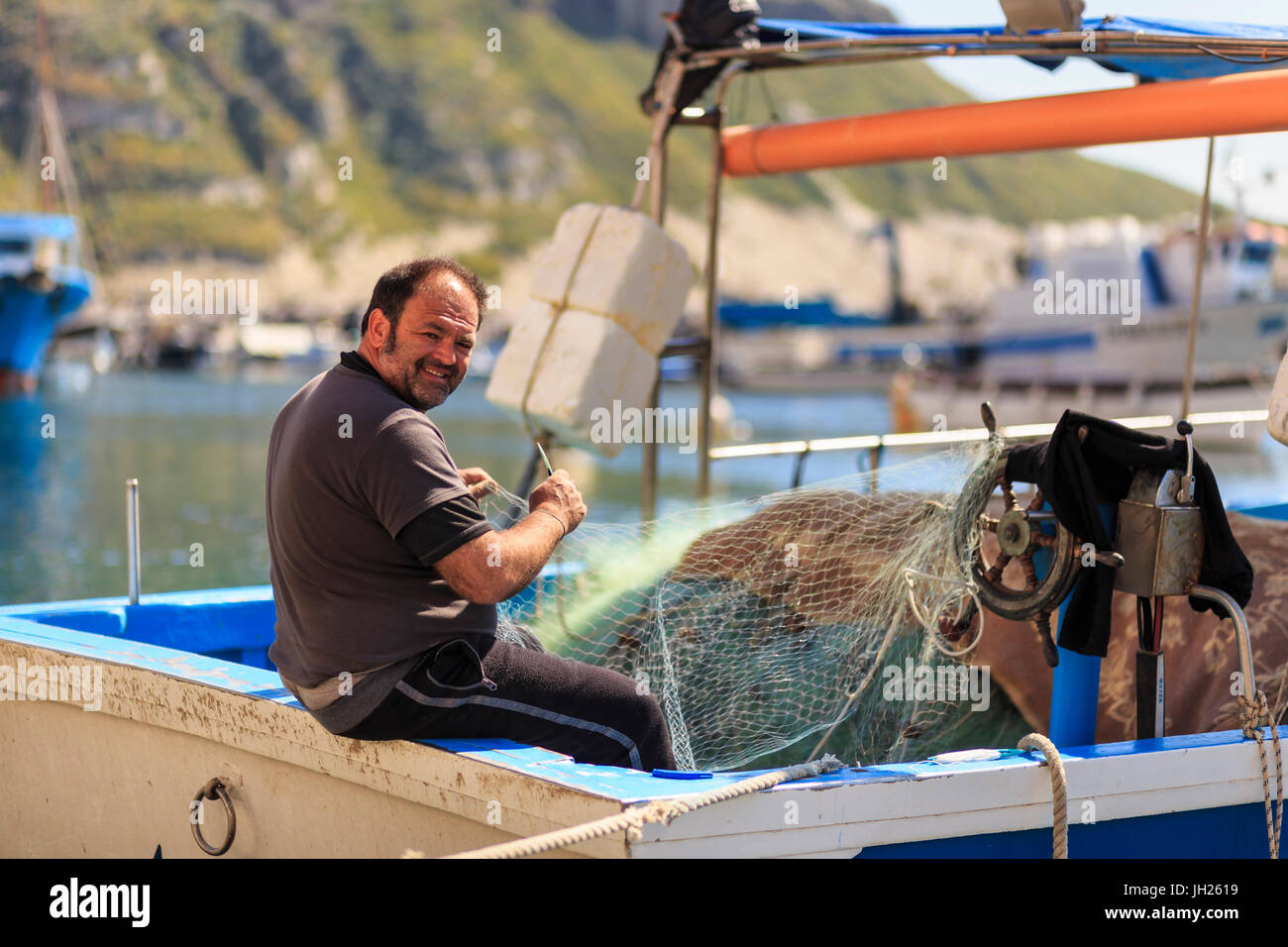 Marina Corricella harbour, smiling fisherman mending fishing nets on a boat, Procida Island, Bay of Naples, Campania, Stock Photo