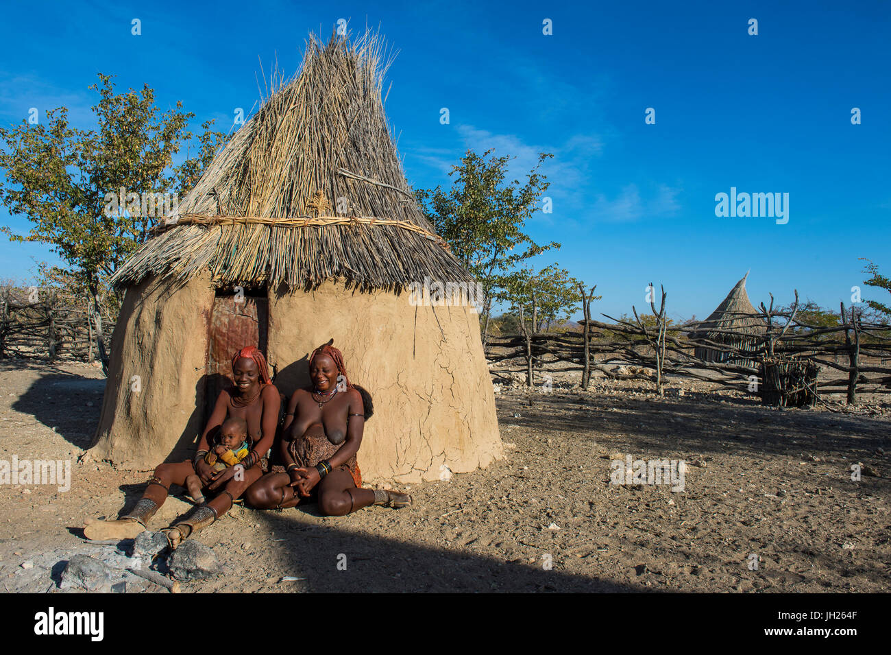 Himba women in front of their hut, Kaokoland, Namibia, Africa - Stock Image