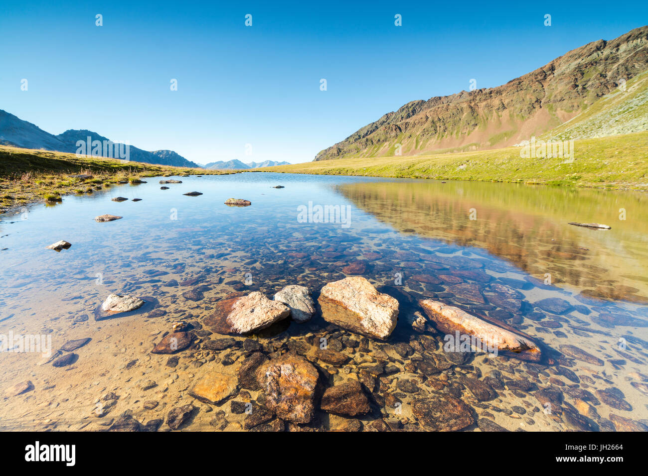 Sun shines on the rocky peaks reflected in the clear water of Lake Umbrail, Stelvio Pass, Valtellina, Lombardy, Stock Photo