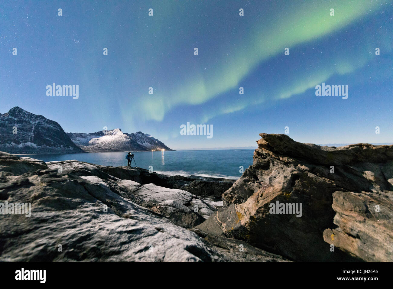 Photographer under the stars and Northern Lights surrounded by rocky peaks and icy sea, Tungeneset, Senja, Troms, - Stock Image