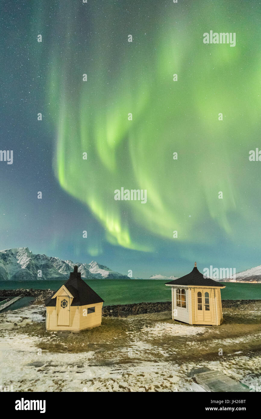 The Northern Lights and stars illuminate the wooden huts by icy sea, Djupvik, Lyngen Alps, Troms, Norway - Stock Image