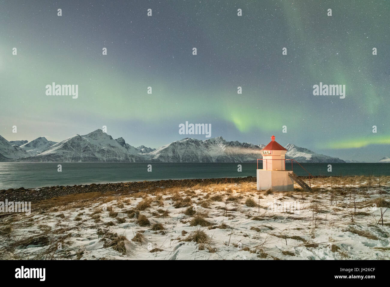 The Northern Lights and stars illuminate the lighthouse framed by icy sea, Djupvik, Lyngen Alps, Troms, Norway - Stock Image