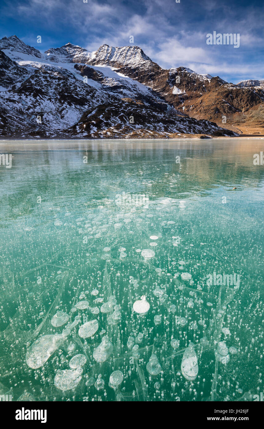 Ice bubbles in the turquoise water of the frozen White Lake (Lago Bianco), Bernina Pass, Canton of Graubunden, Switzerland - Stock Image