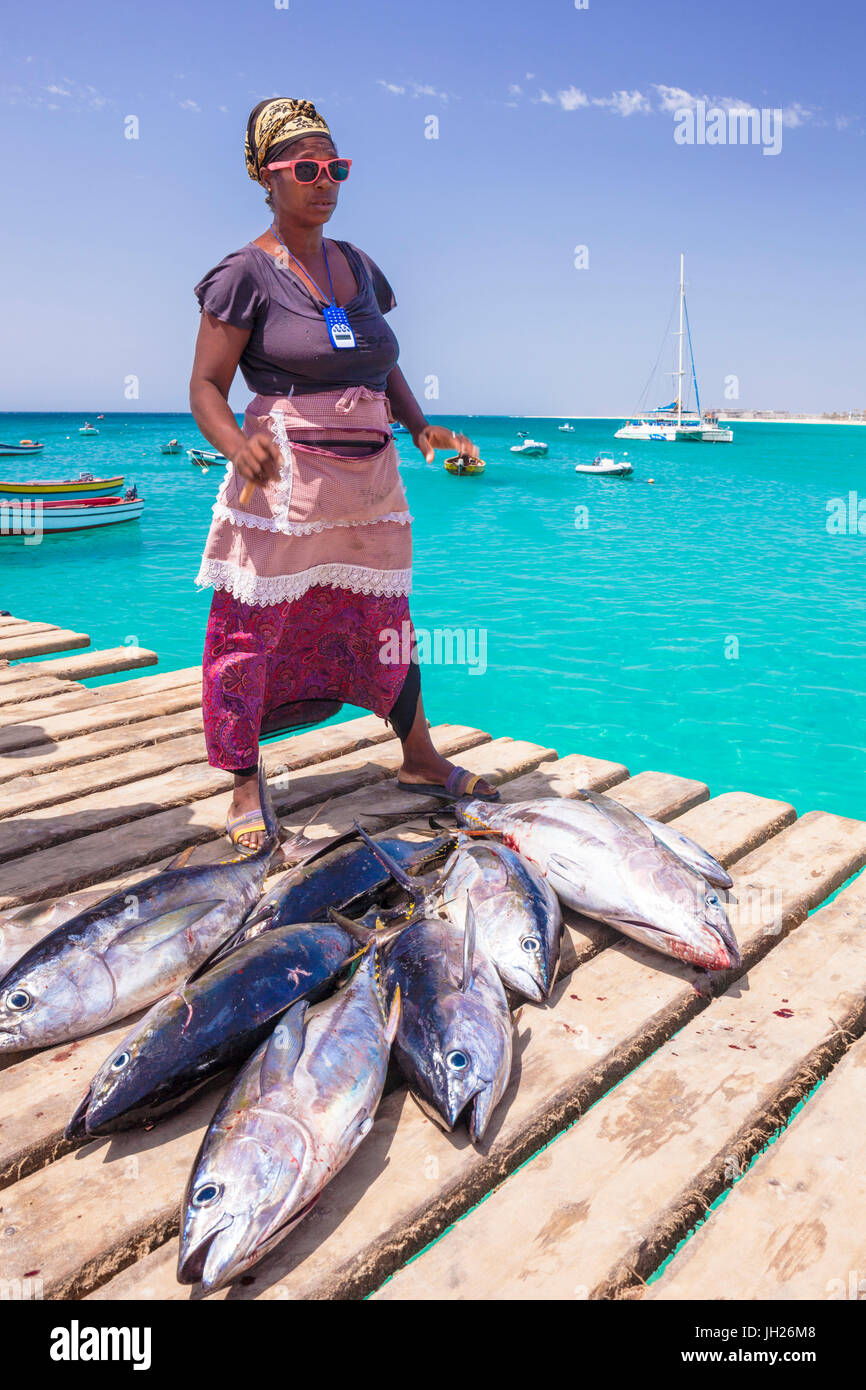 Colourful local woman selling freshly caught yellow fin tuna fish from the pier at Santa Maria, Sal island, Cape Stock Photo