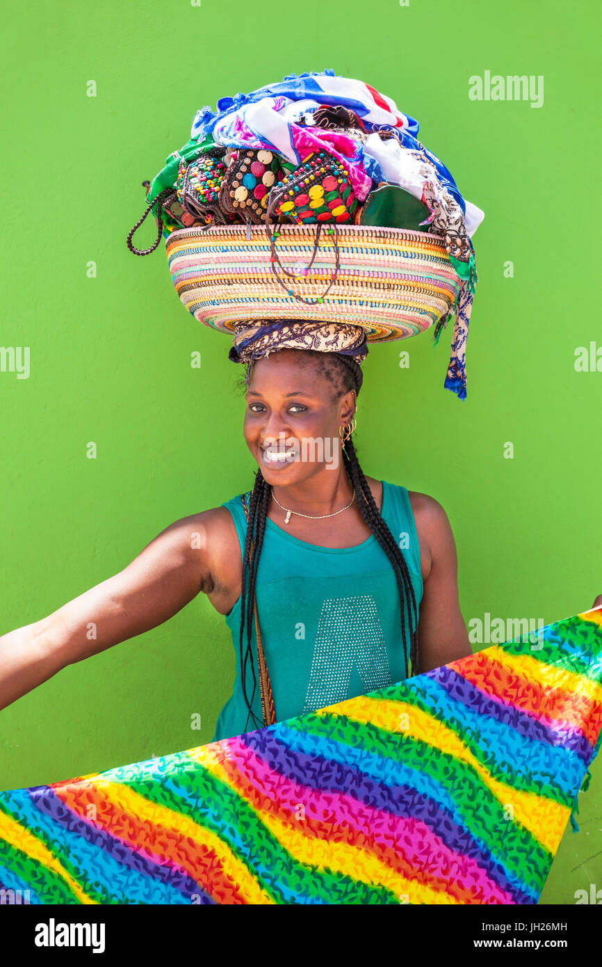 Local woman with basket on her head selling souvenir scarves and jewellery, Espargos, Santa Maria, Sal island, Cape - Stock Image