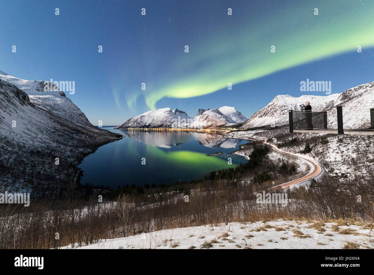 Photographer on platform admires the Northern lights and stars reflected in the cold sea, Bergsbotn, Senja, Troms, - Stock Image