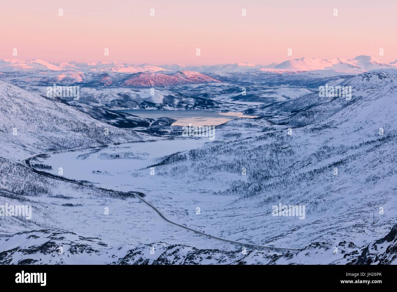 Pink sky at sunset on the snowy landscape and frozen sea surrounding Fjordbotn, Lysnes, Senja, Troms, Norway, Scandinavia - Stock Image