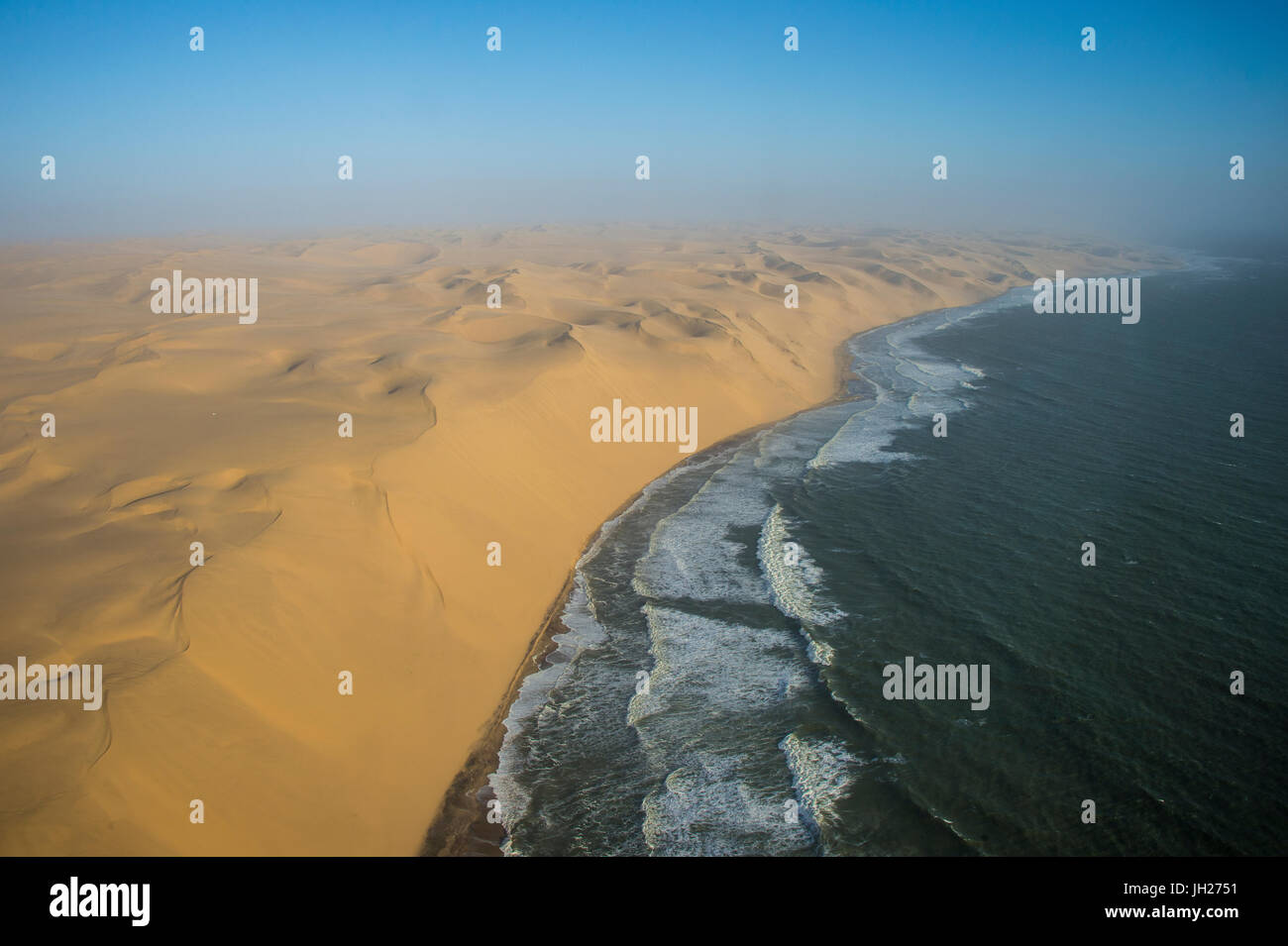 Aerials of sand dunes of the Namib Desert meeting the Atlantic Ocean, Namibia, Africa - Stock Image
