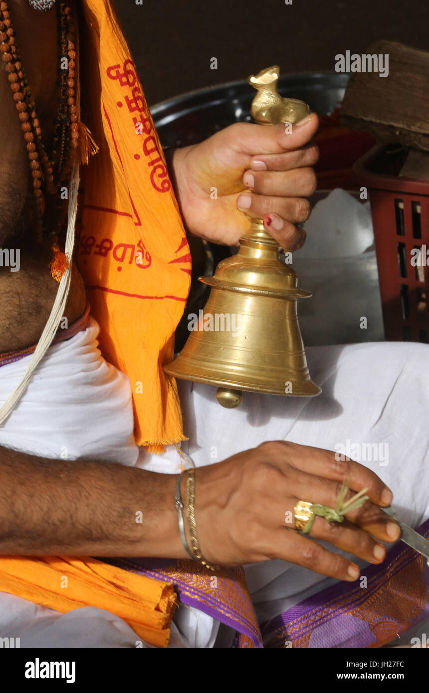 Hindu priest. Close up of hand holding ceremonial bell.  Singapore. - Stock Image