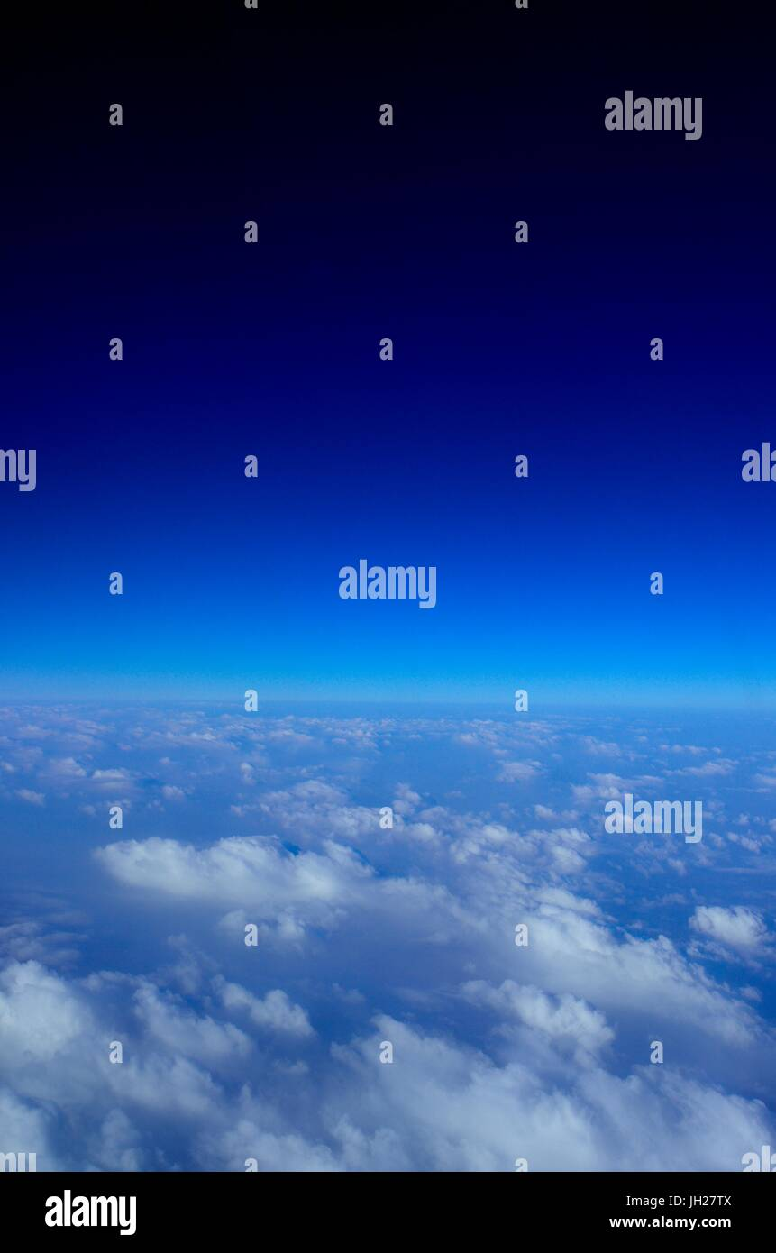 Beautiful view of the clouds below and deep Blue Sky above as seen from an aircraft window Stock Photo