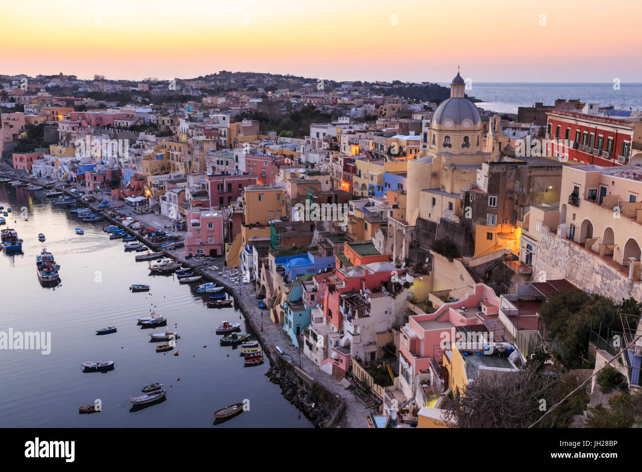 Marina Corricella, blue hour after sunset, fishing village, colourful houses, boats and church, Procida, Bay of - Stock Image
