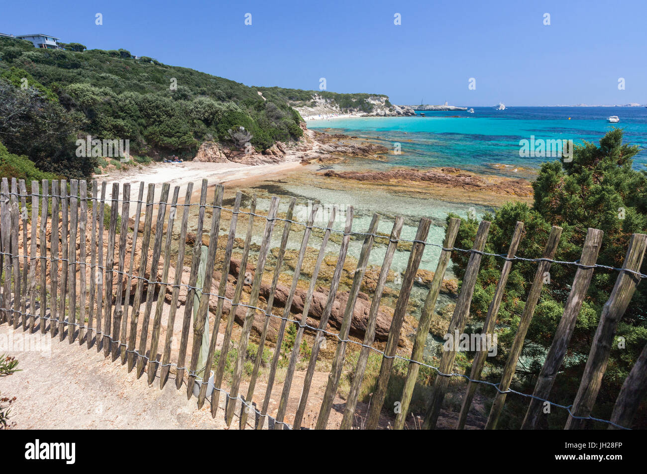 The wooden fence frames the limestone rocks and turquoise sea, Sperone, Bonifacio, South Corsica, France, Mediterranean, - Stock Image