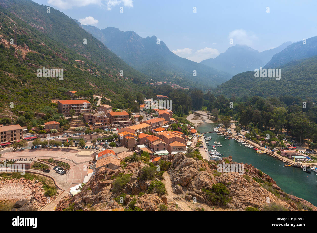 The typical village and harbor of Porto immersed in the green vegetation of the promontory, Southern Corsica, France - Stock Image