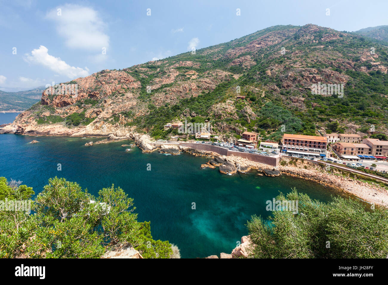 Top view of turquoise sea framed by green vegetation and the typical village of Porto, Southern Corsica, France, - Stock Image