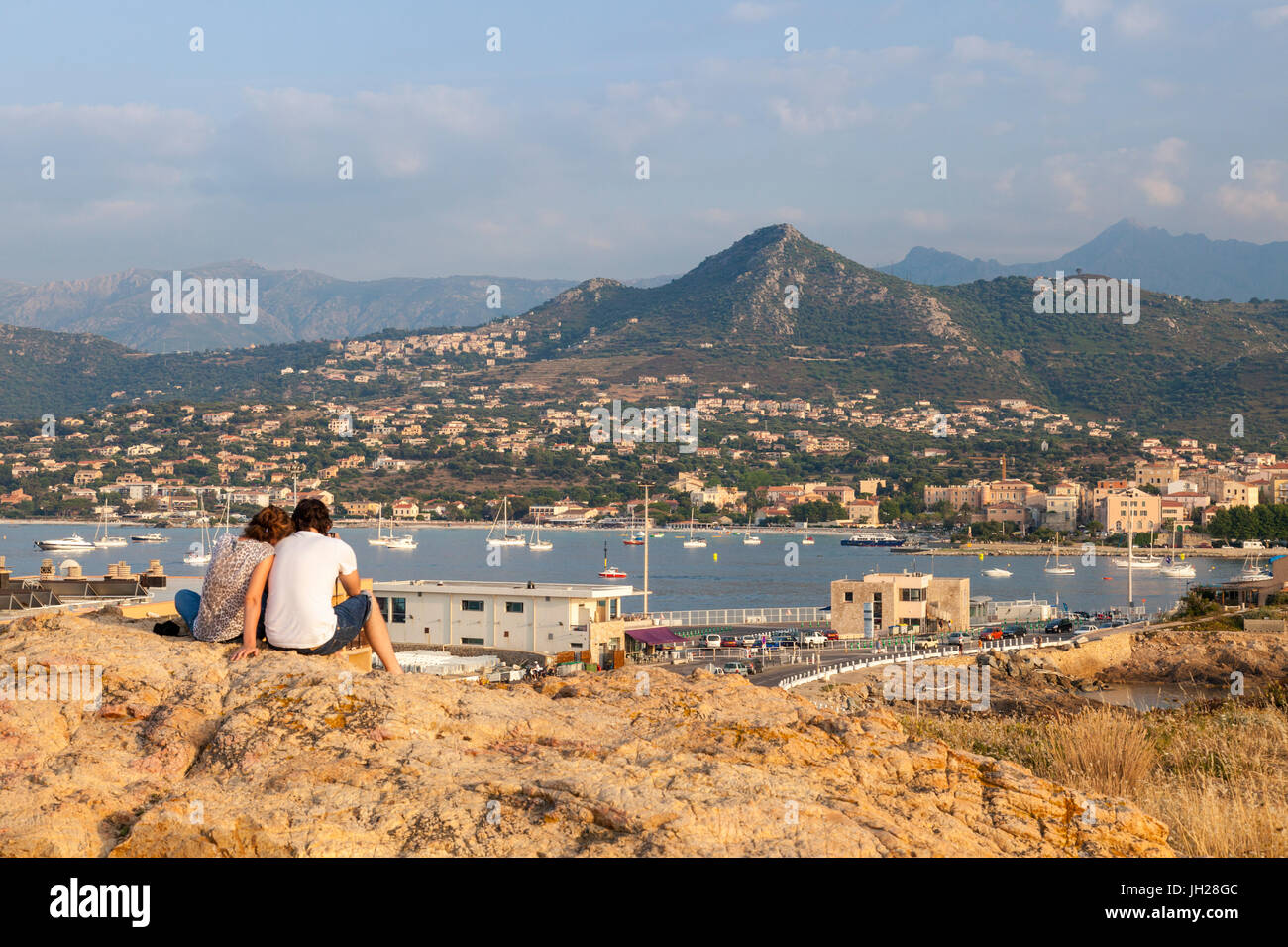 Tourists admire the sea and sail boats around the village of Ile Rousse, Balagne Region, Corsica, France, Mediterranean, - Stock Image