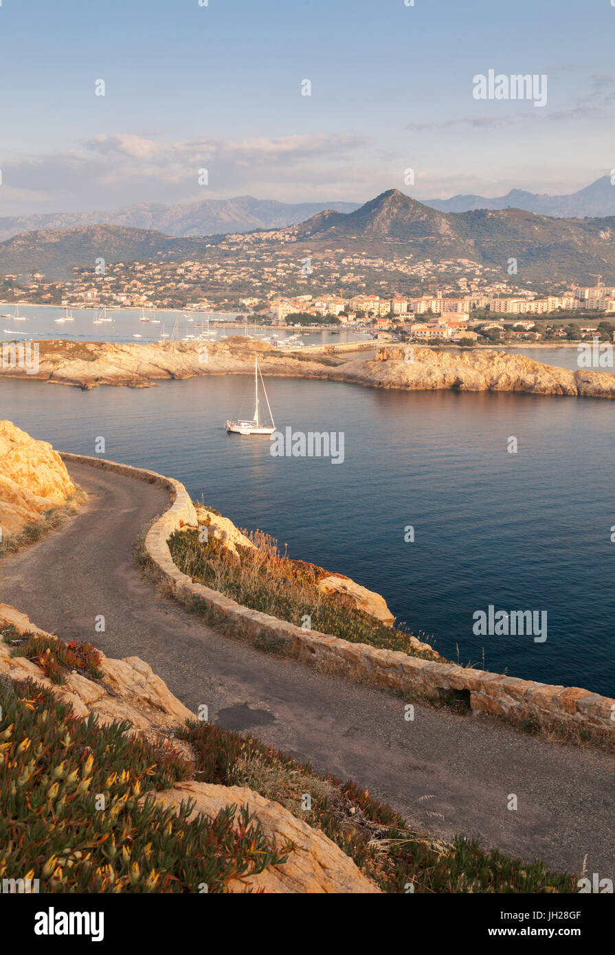 A sail boat in the clear sea around the village of Ile Rousse at sunset, Balagne Region, Corsica, France, Mediterranean, - Stock Image