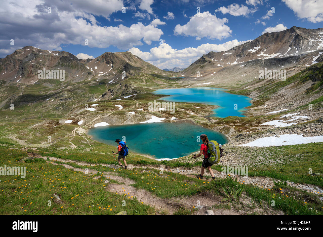 Hikers pass the turquoise lake and rocky peaks, Joriseen, Jorifless Pass, canton of Graubunden, Engadine, Switzerland, - Stock Image
