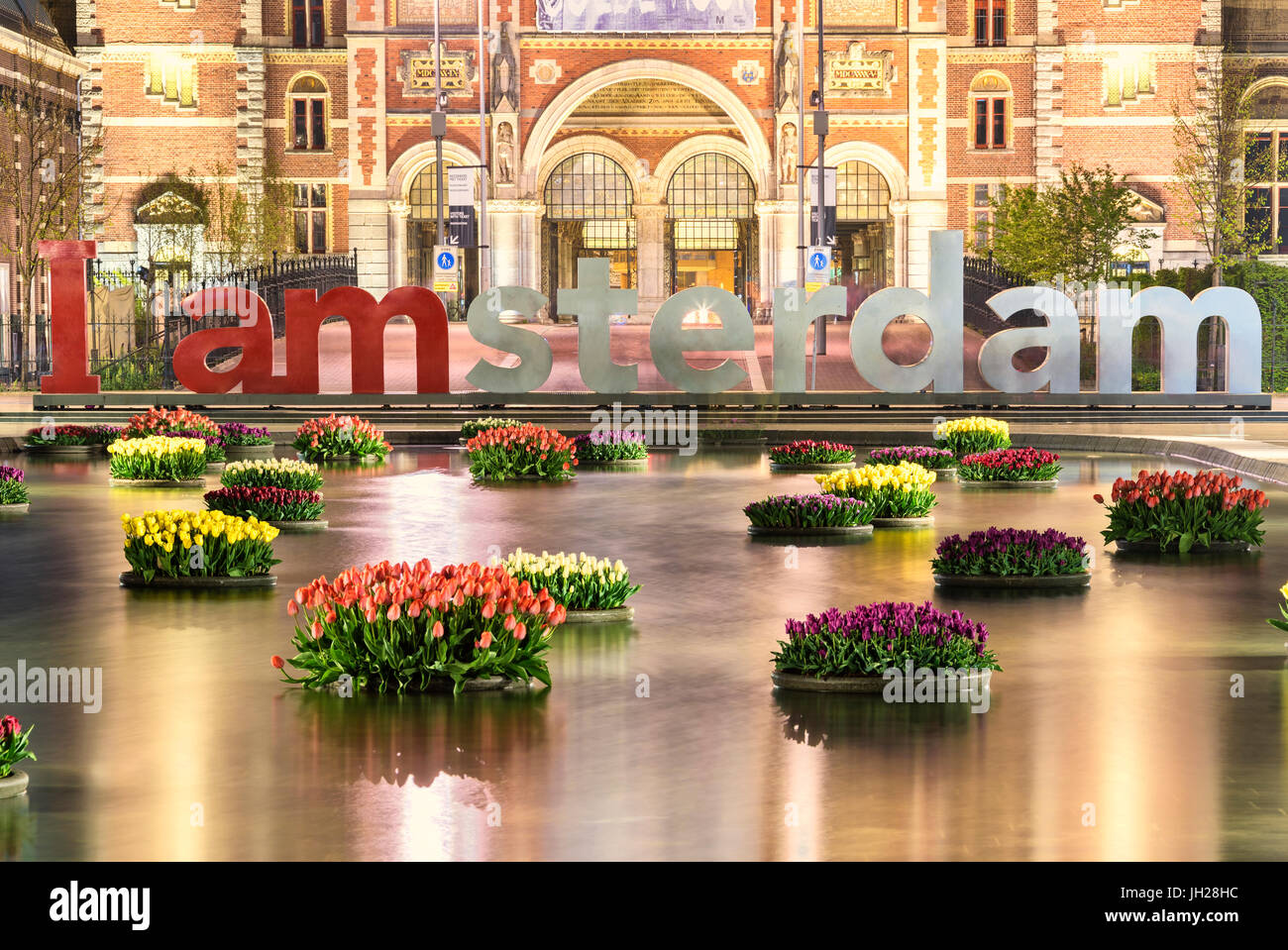 The National Rijksmuseum framed by vases of flowers floating in water, Amsterdam, Holland, The Netherlands, Europe - Stock Image