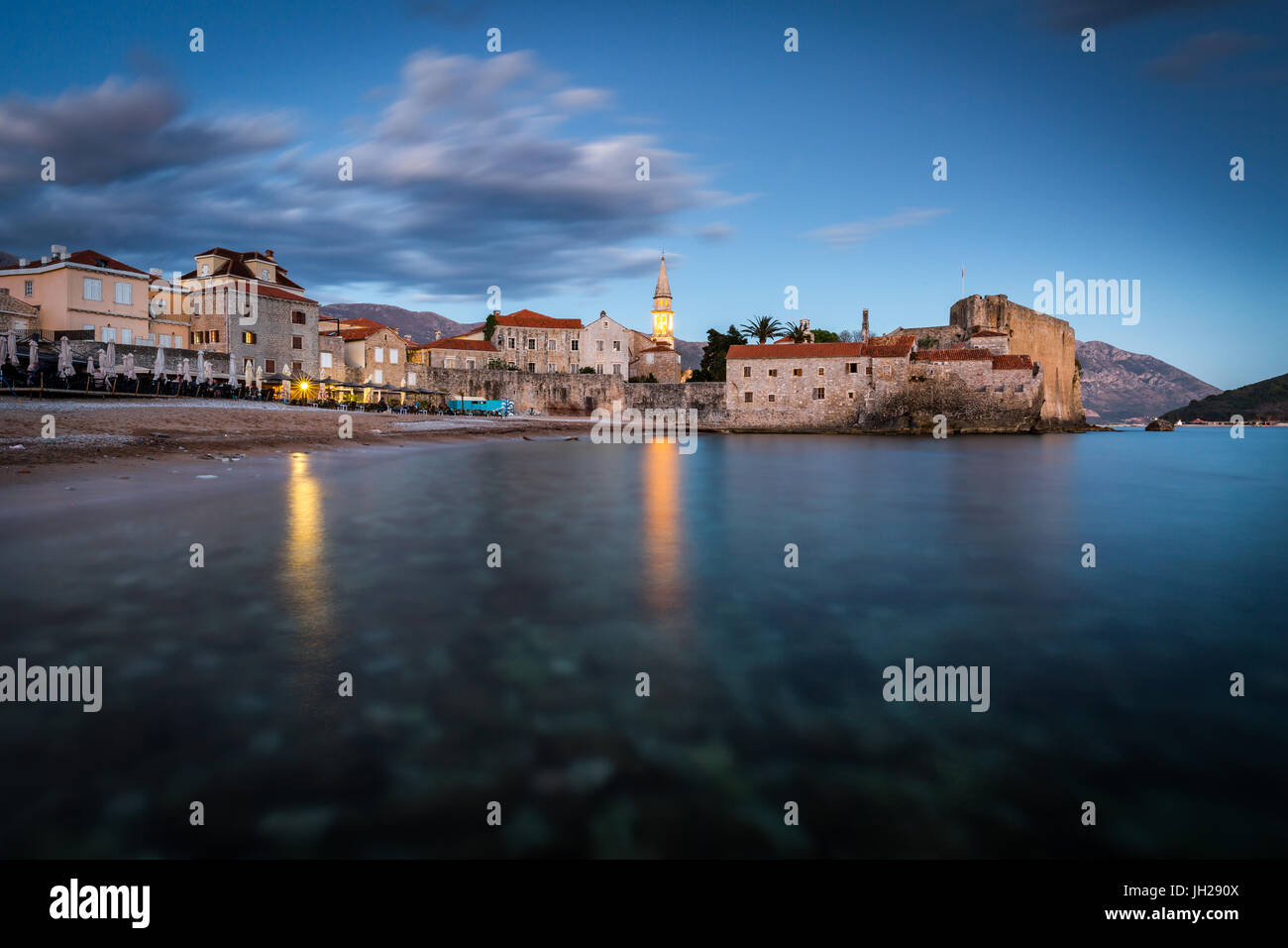 A long exposure during the evening blue hour of the beach and stari grad (old town) of Budva, Montenegro, Europe - Stock Image