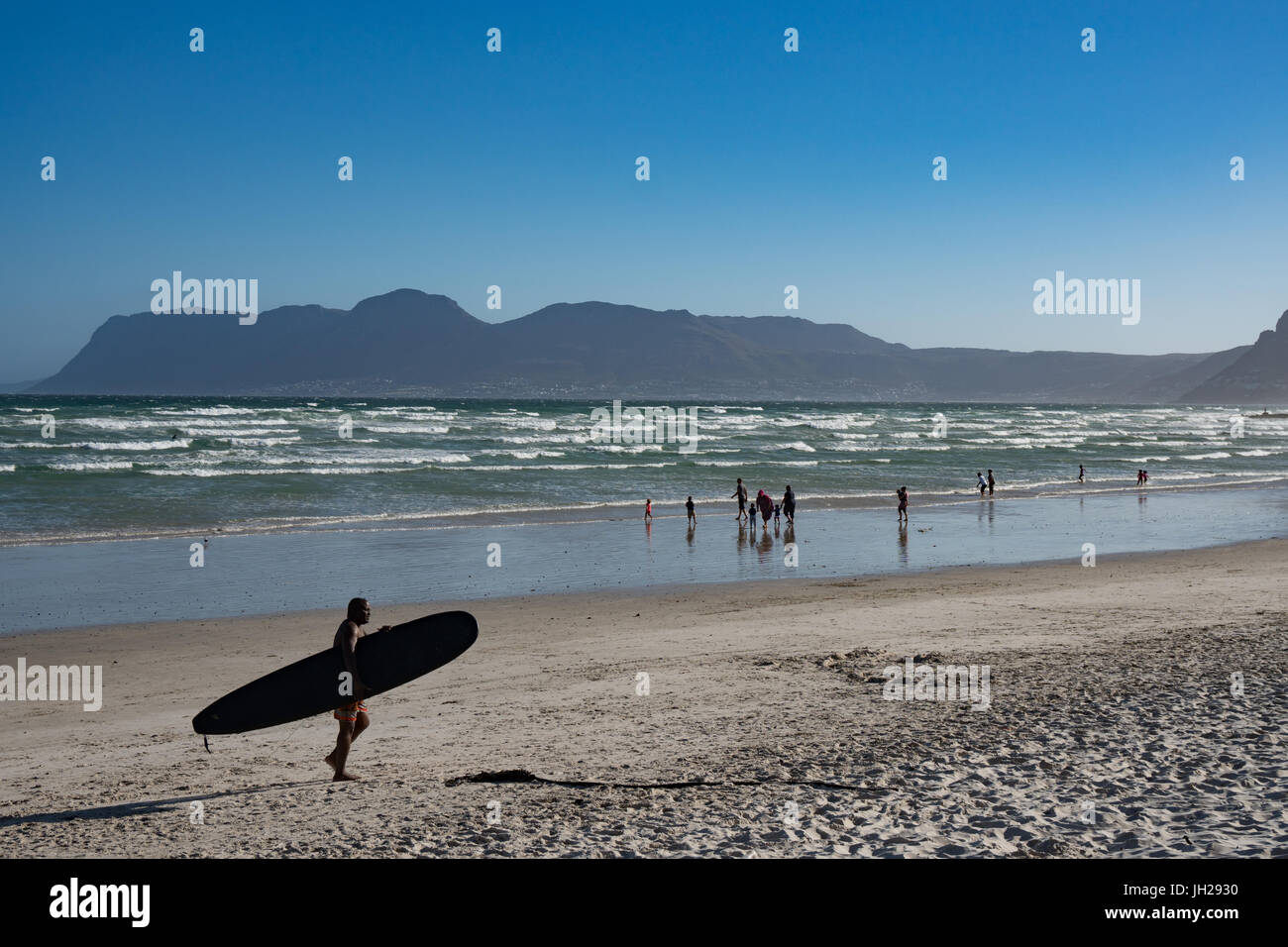 Surfer returning across beach with surfboard, False Bay, Cape Town, South Africa, Africa - Stock Image