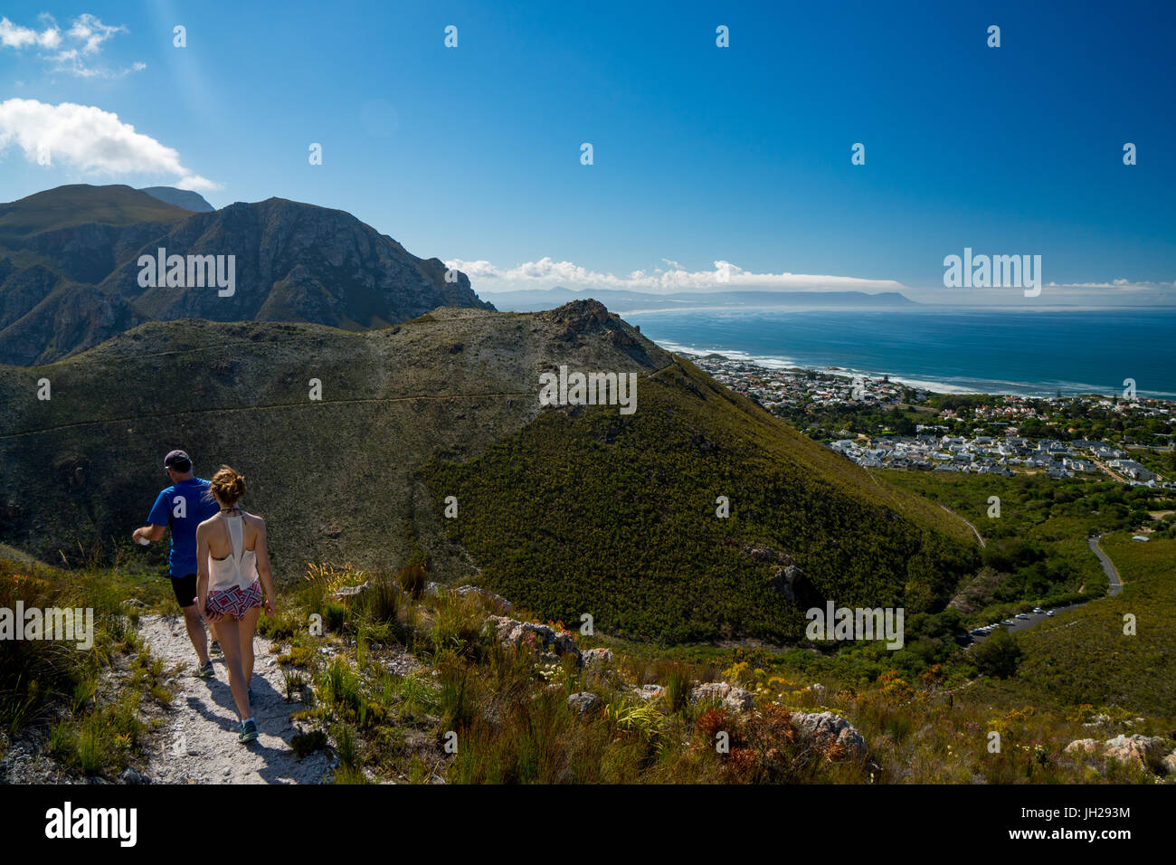 Man and woman hikers walking down into Hermanus from the mountain, Hermanus, South Africa, Africa - Stock Image