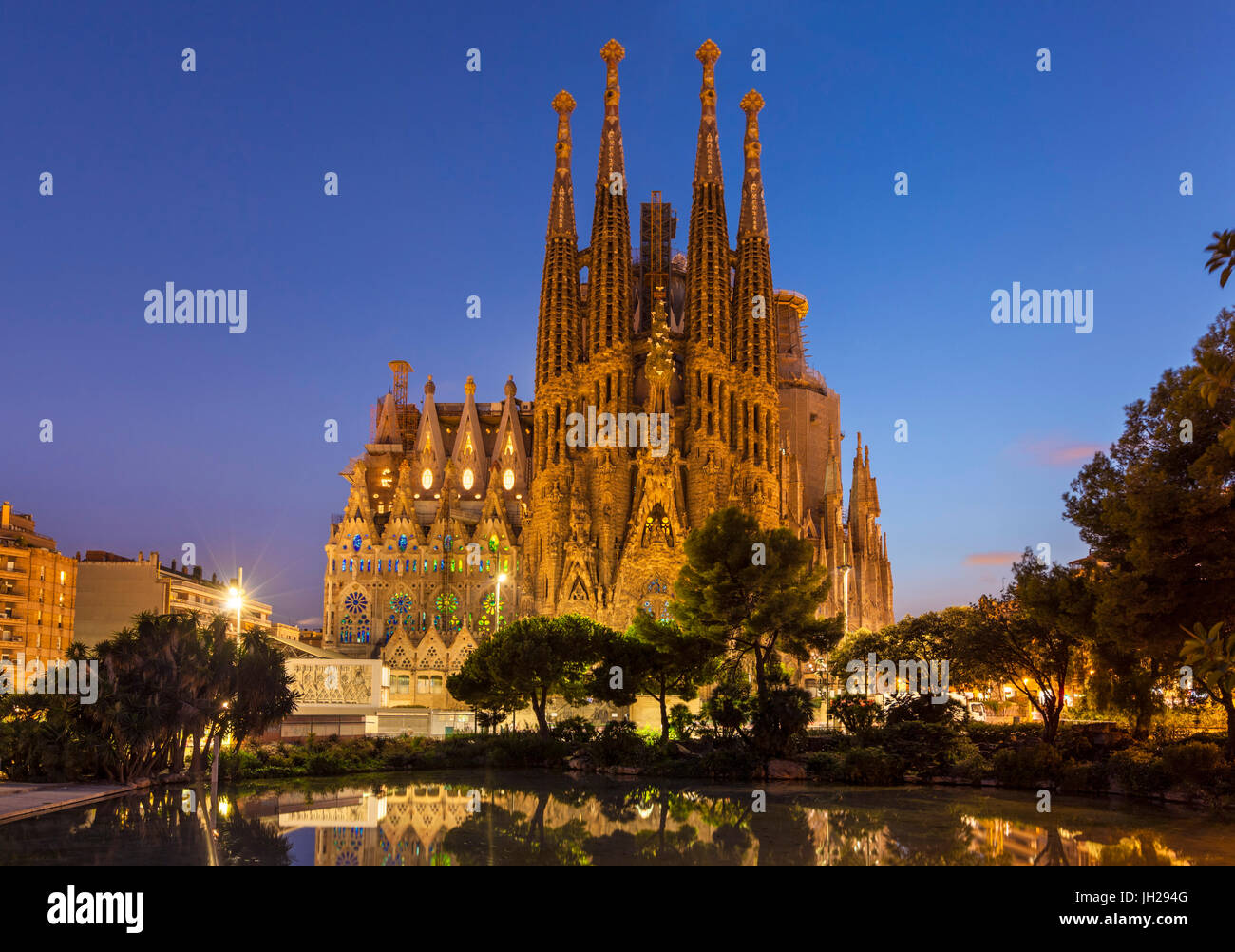 La Sagrada Familia church lit up at night designed by Antoni Gaudi, UNESCO, reflected in pool, Barcelona, Catalonia, - Stock Image