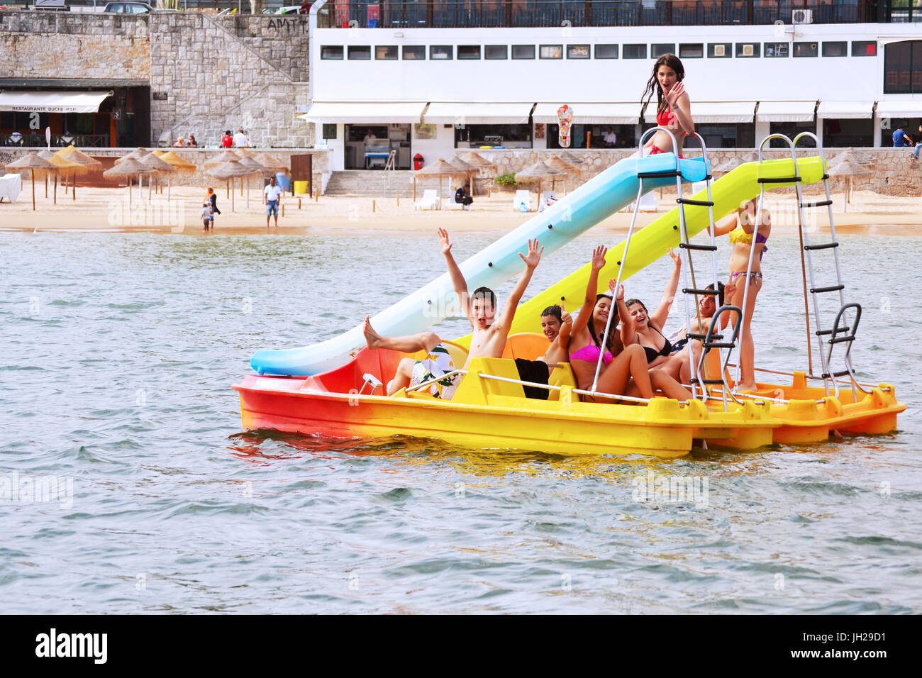 A group of teenagers having fun on a floating water slide near the beach during Summer in Cascais, Portugal. - Stock Image