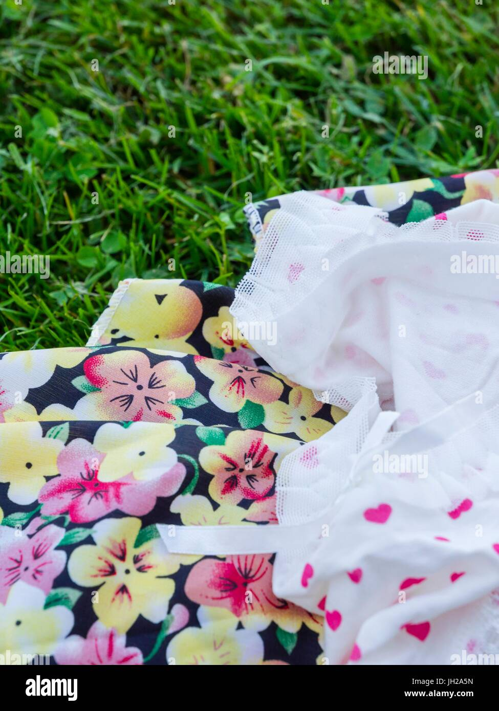 Colorful summer dress and knickers left on grass-field field grass - Stock Image