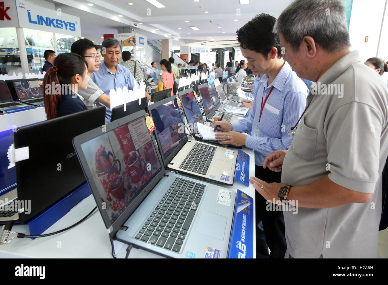Electronics shop. Shop Assistant Helping a Customer With a Laptop.  Ho Chi Minh City. Vietnam. - Stock Image