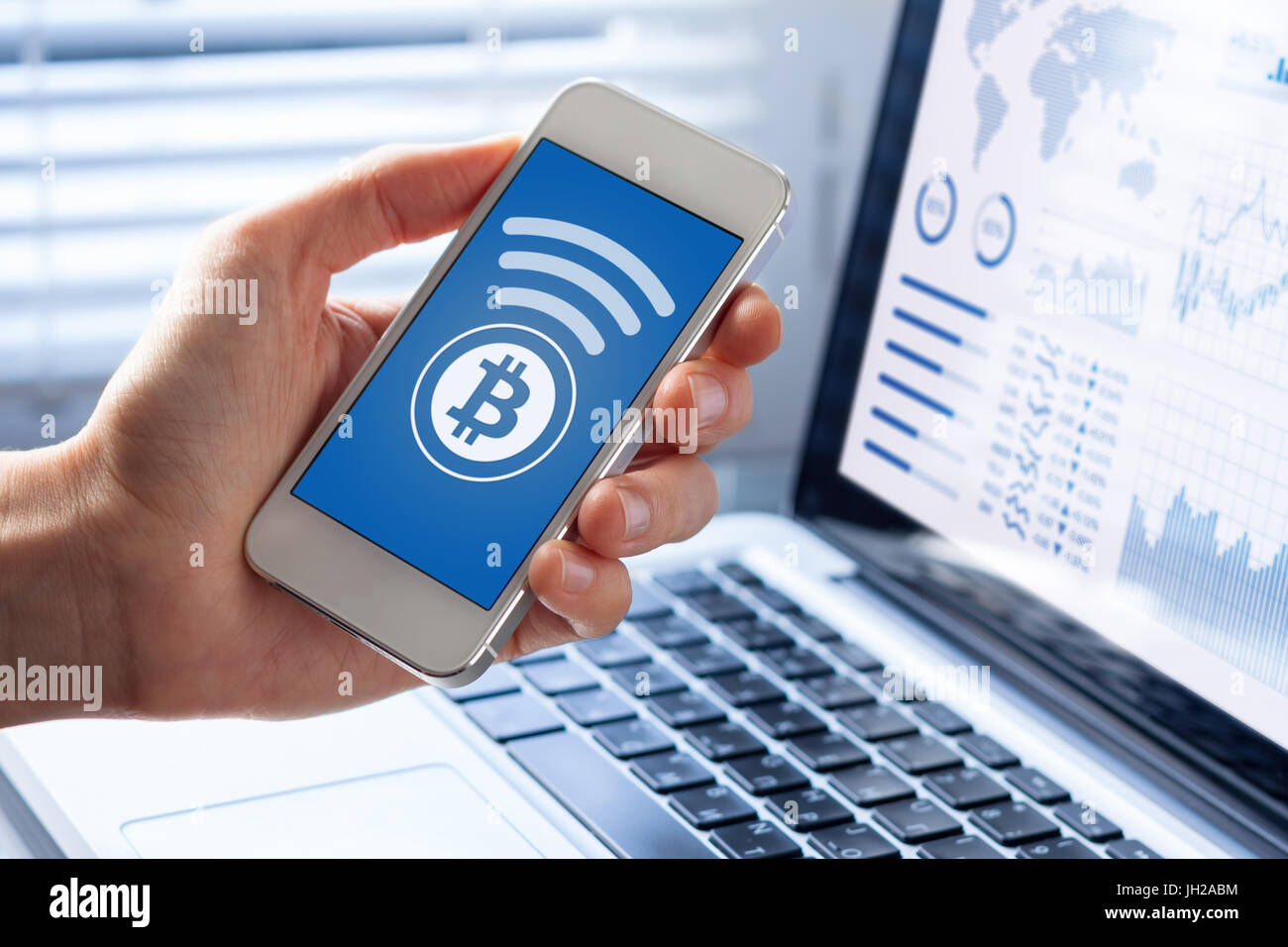 Person sending bitcoin with smartphone for online payment, closeup of mobile phone screen, business office background - Stock Image