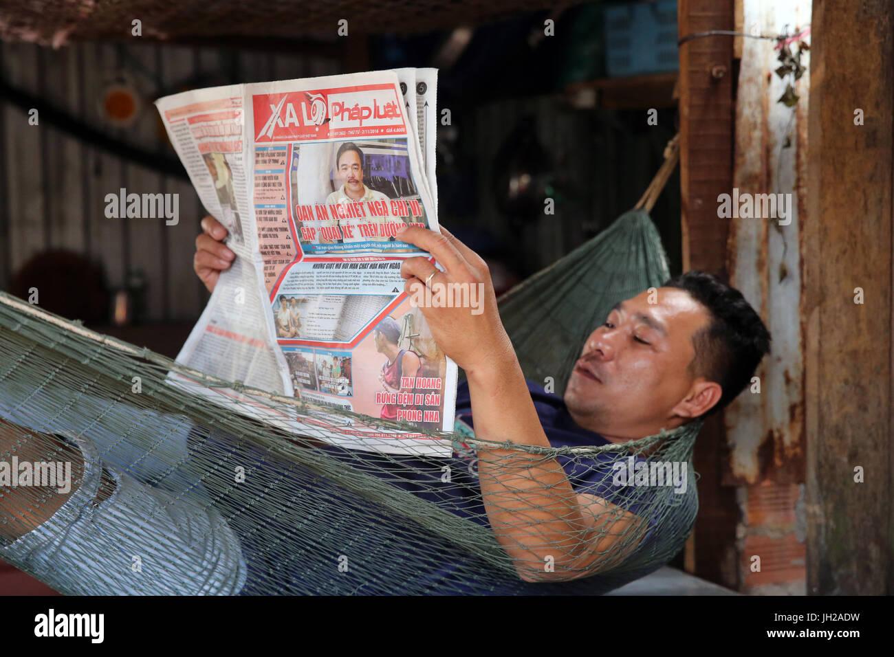 Man reading newspaper in a Hammock.  Vietnam. - Stock Image