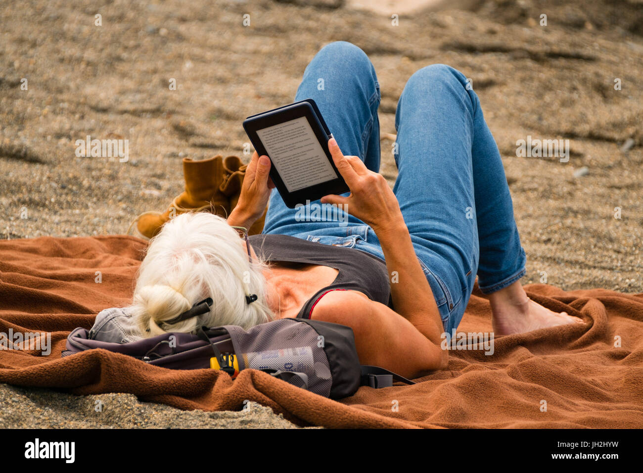 Woman Reading Kindle Book At The Seaside Stock Photos