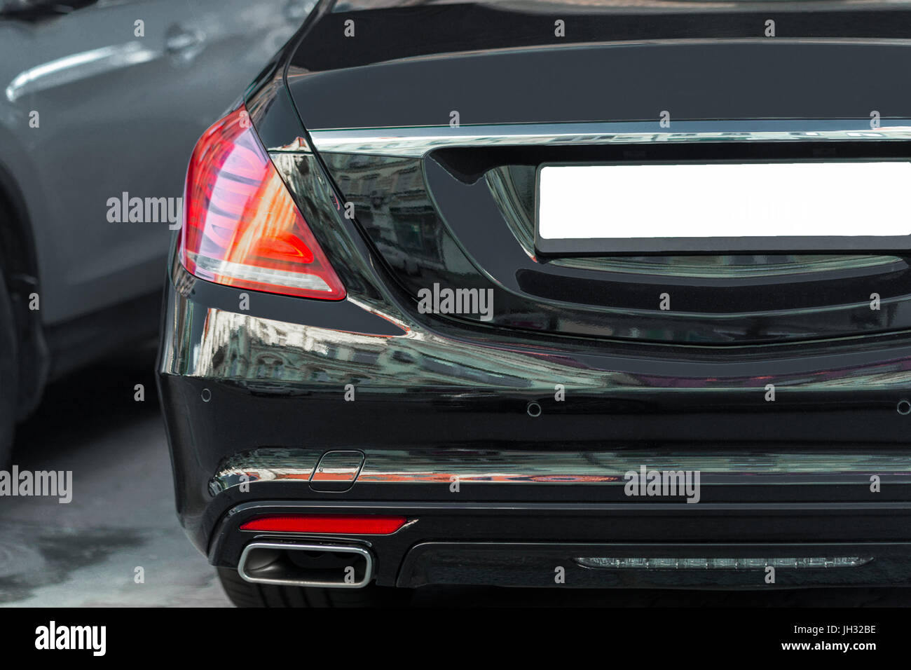 Back view of big luxury expensive sedan car trunk. Black colored. LED red tail lights . Empty license plate with - Stock Image