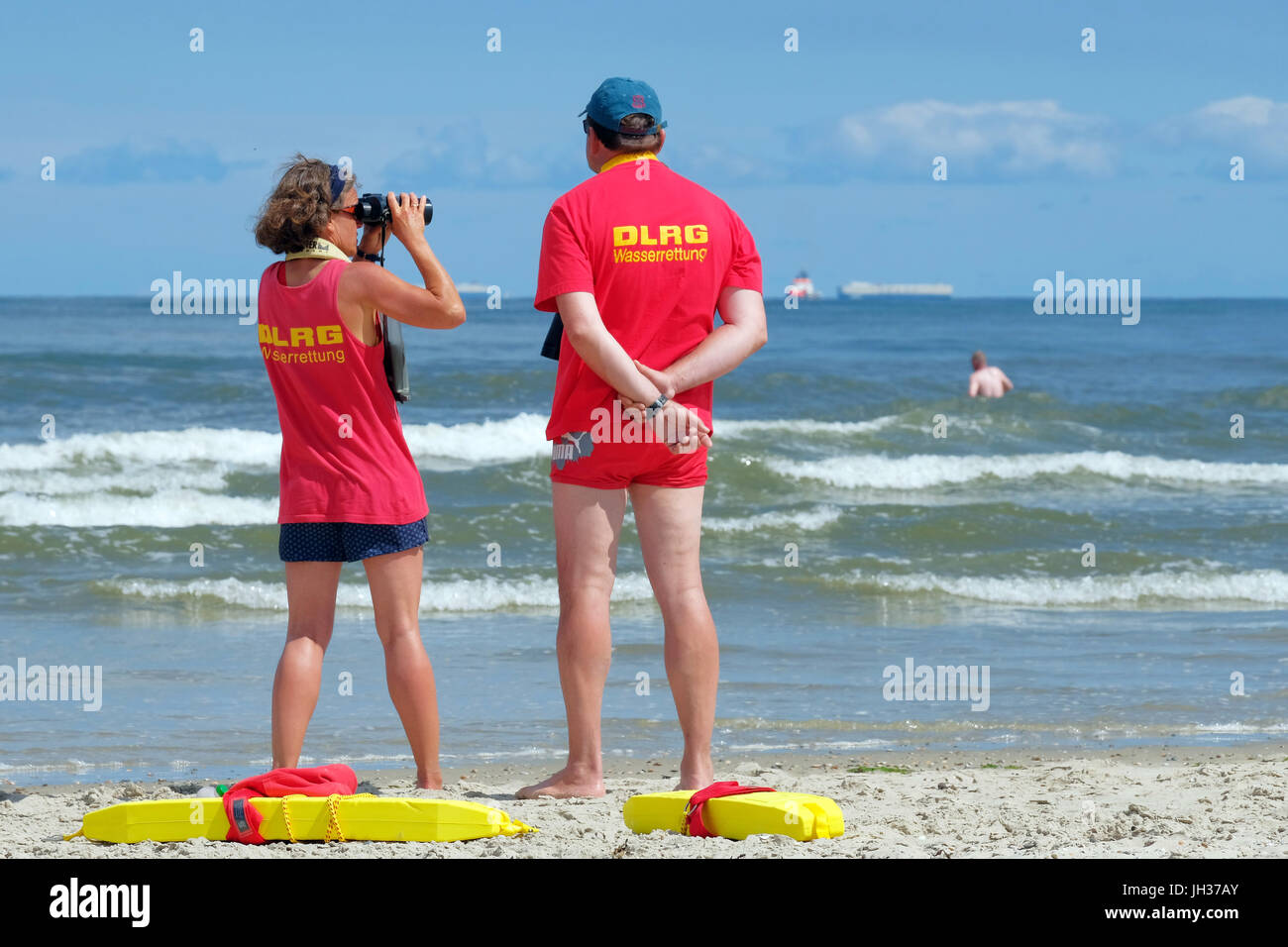 Members of the DLRG German Life Saving Society watch swimmer in the waves of the North Sea on the beach of the island Stock Photo