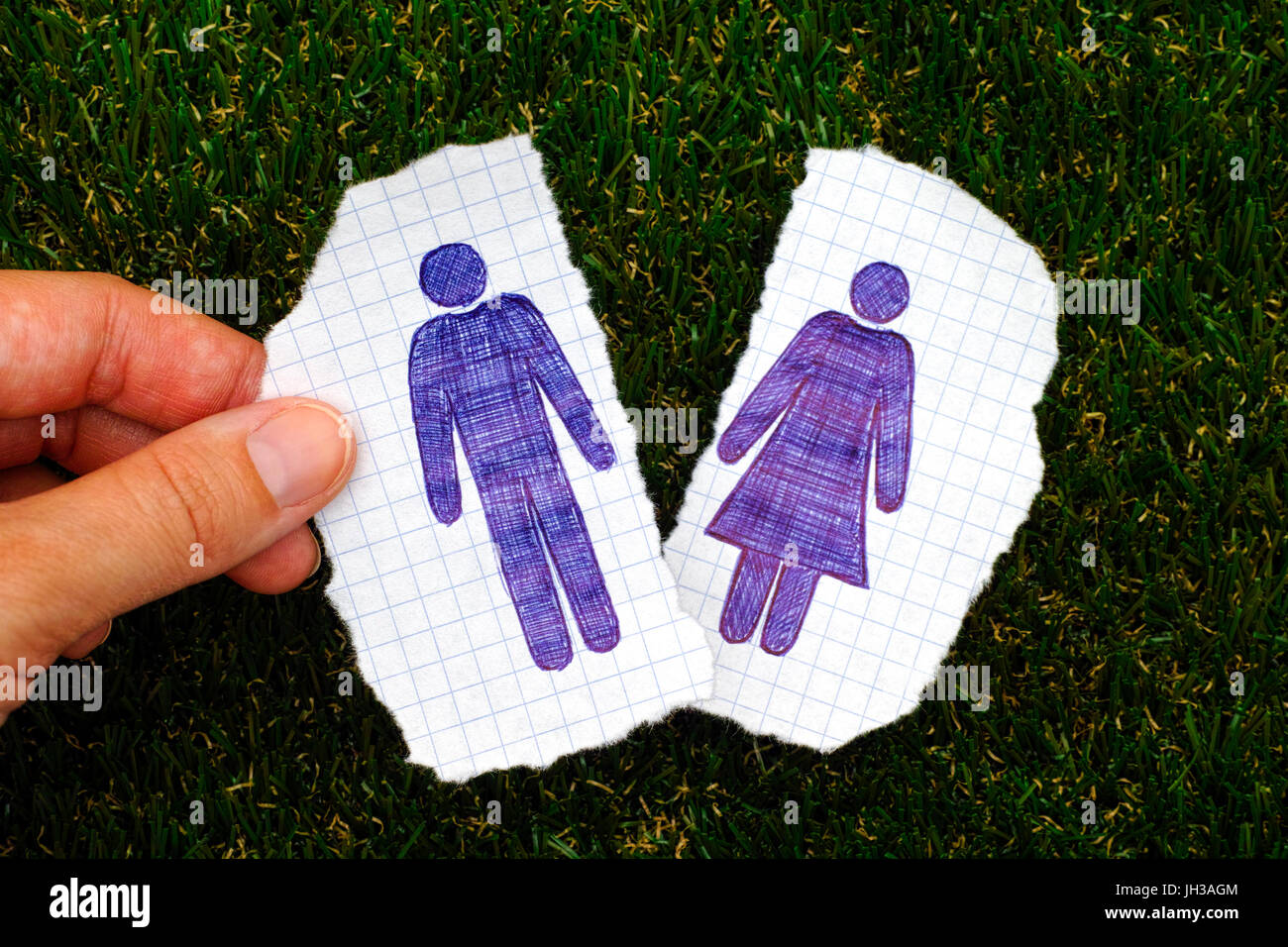 Woman fingers holding piece of paper with hand drawn man figure. Other piece of paper with drawn woman figure on - Stock Image
