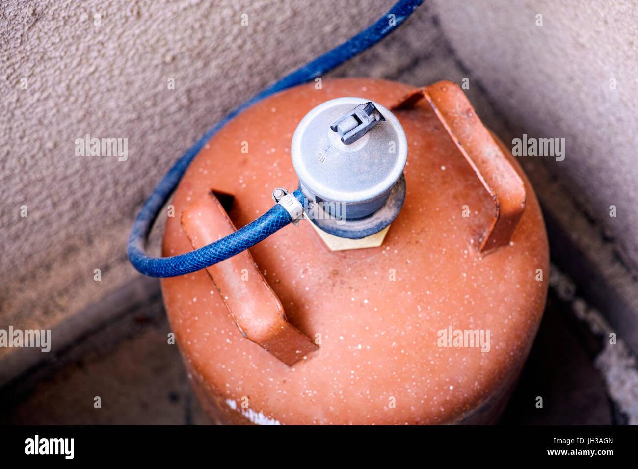 Orange gas bottle with gas regulator stay in corner. - Stock Image