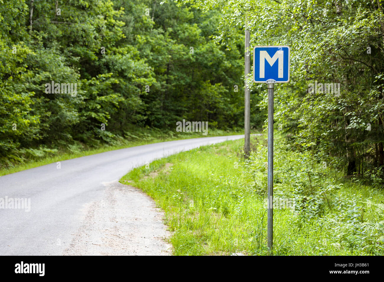 Blue and white letter M sign symbols passing place on swedish single track road in Sweden  Model Release: No.  Property - Stock Image
