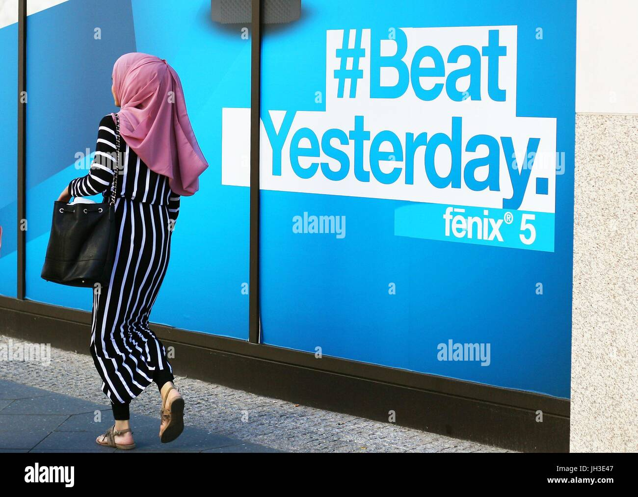"""A young Muslim woman walks by a shopping center and a giant advertising reading """"#Beat Yesterday""""  in central Berlin Stock Photo"""