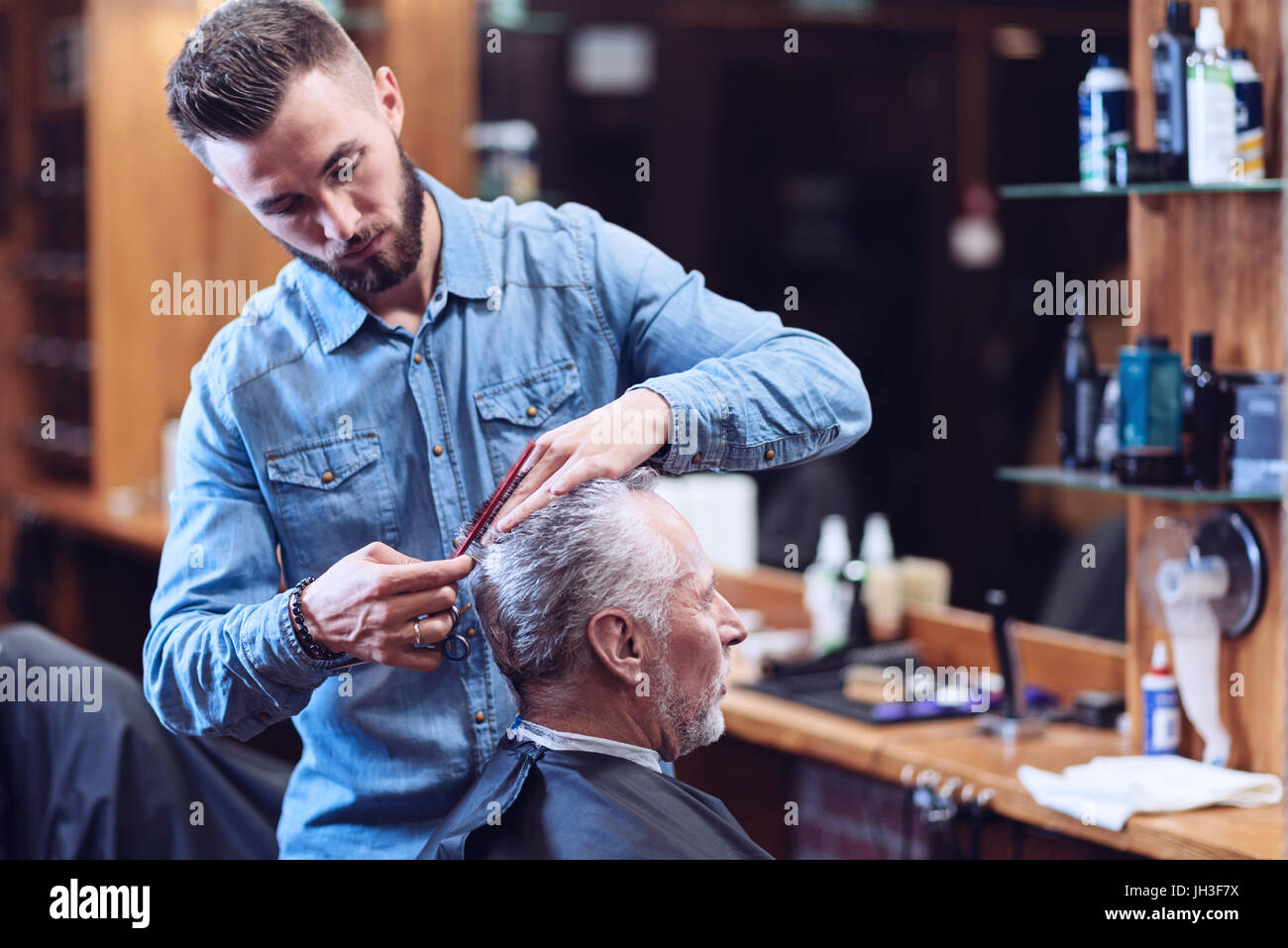 Serious professional hairdresser being involved in his job - Stock Image