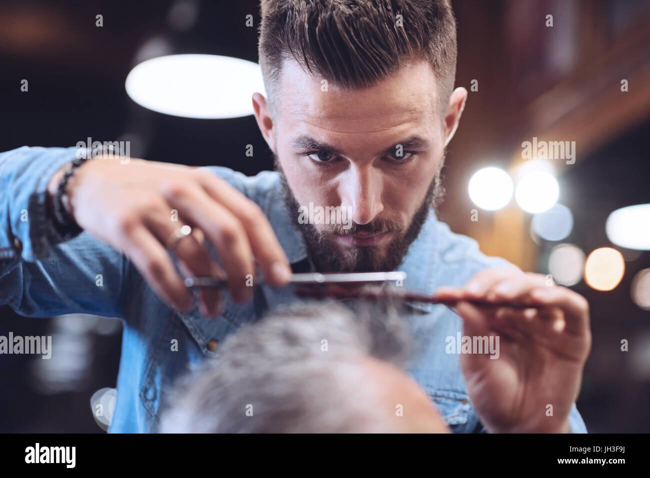 Nice bearded barber doing his job - Stock Image